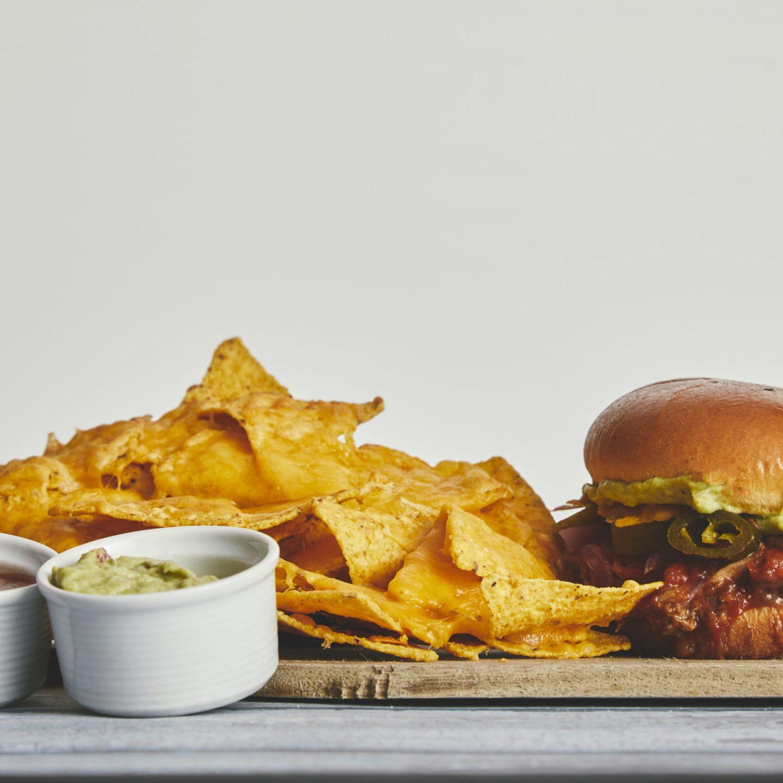 Lunas burger med nachos eller fries 125,- ( med pork carnitas, guacamole, syltede rødløg, bønnemos, grillet ost, chipotle sovs, jalapeños)